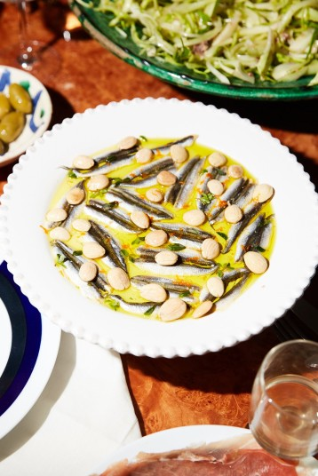 A plate of white anchovies in olive oil topped with marcona almonds, marjoram and orange zest.CreditPaul Quitoriano