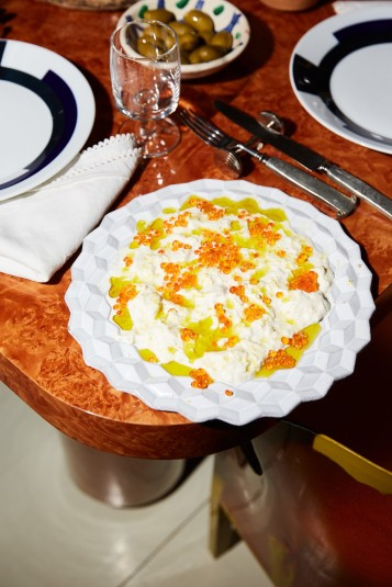 Stracciatella di bufala drizzled with olive oil and covered with salmon roe.CreditPaul Quitoriano